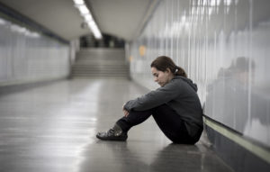 young sad woman in pain alone and depressed at urban subway tunnel ground worried suffering depression