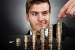Young Businessman Stacking Coins At Desk
